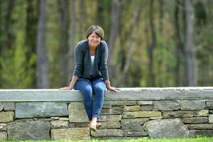 """Jennifer Hubbard sits in the Catherine Violet Hubbard Animal Sanctuary. Hubbard has written a book, """"Finding Sanctuary"""" and is the executive director of the animal sanctuary which she founded in memory of her daughter who died in the Sandy Hook Elementary School shooting. Friday afternoon, May 7, 2021, in Newtown, Conn."""