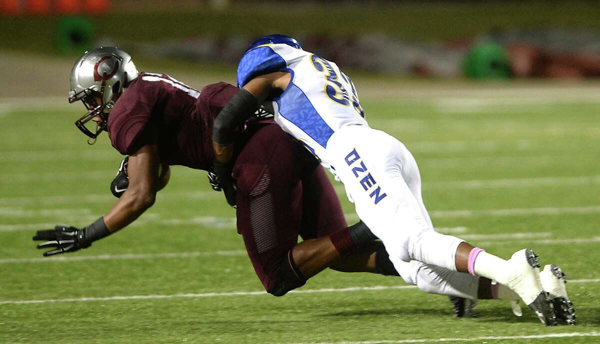 Central's Devwah Whaley is tackled by Ozen's Markel Perry as he carries the ball during the annual Soul Bowl Friday night at the Thomas Center. The rivalry extends well beyond the playing field, with bands and fans looking to outdo one another in what is a highlight of Beaumont high schools' legendary rivalry. Photo taken Friday, October 16, 2015 Kim Brent/The Enterprise