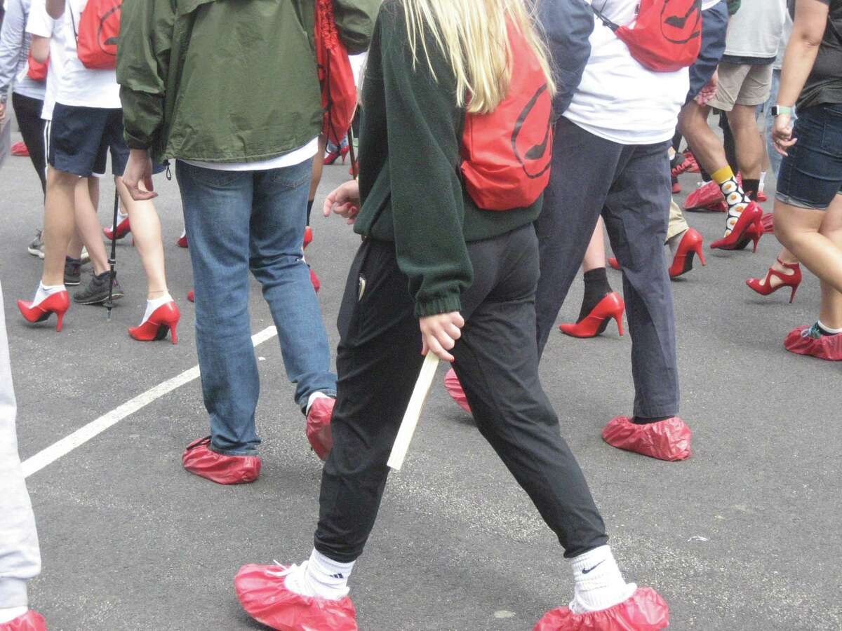 Participants in the Walk a Mile in Her Shoes fundraiser and awareness event show their red shoes May 19, 2019 on the Litchfield Green. This year's walk is virtual and starts May 17; teams and individuals are encouraged to sign up now.