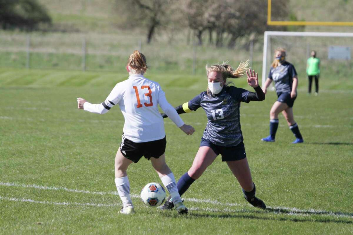 Manistee senior Olivia Smiththreadsthe ball through a defender's legs during the Chippewas' victory over Kingsley on Friday at Chippewa Field. (Dylan Savela/News Advocate)