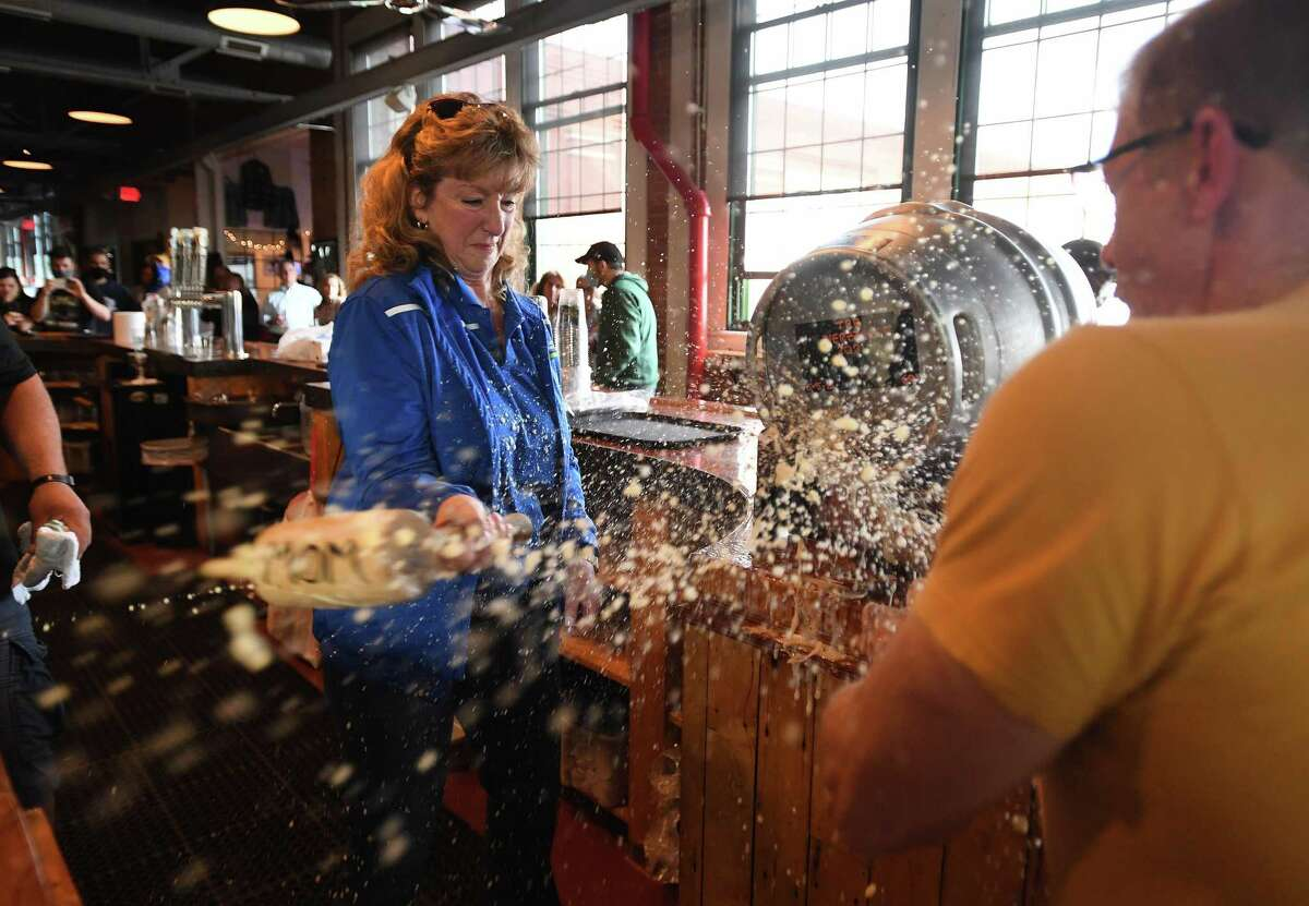 Beer flies through the air as Stratford Mayor Laura Hoydick taps a keg of Herzzoner, the company's seasonal Maibock beer, with the help of company founder and CEO Brad Hittle at Two Roads Brewing Company in Stratford on Thursday.