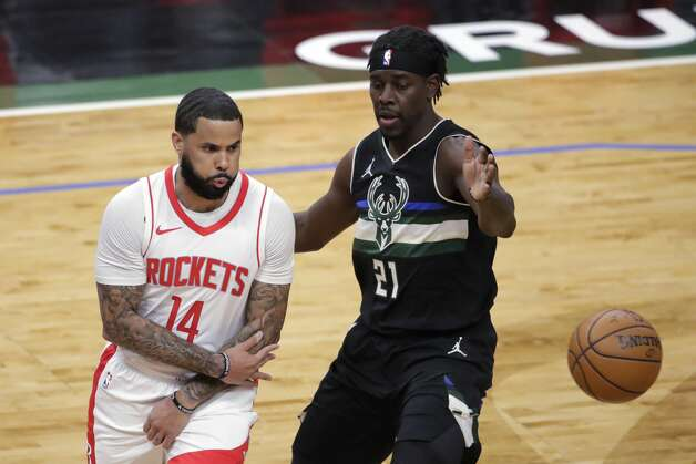 Houston Rockets' D.J. Augustin (14) passes the ball around Milwaukee Bucks' Jrue Holiday (21) during the first half of an NBA basketball game Friday, May 7, 2021, in Milwaukee. (AP Photo/Aaron Gash) Photo: Aaron Gash/Associated Press / Copyright 2021 The Associated Press. All rights reserved.