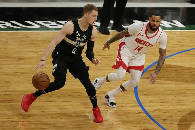 MILWAUKEE, WISCONSIN - MAY 07: Donte DiVincenzo #0 of the Milwaukee Bucks is defended by D.J. Augustin #14 of the Houston Rockets during the first half of a game at Fiserv Forum on May 07, 2021 in Milwaukee, Wisconsin. NOTE TO USER: User expressly acknowledges and agrees that, by downloading and or using this photograph, User is consenting to the terms and conditions of the Getty Images License Agreement. (Photo by Stacy Revere/Getty Images) Photo: Stacy Revere/Getty Images / 2021 Getty Images
