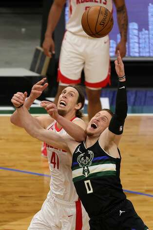 MILWAUKEE, WISCONSIN - MAY 07: Donte DiVincenzo #0 of the Milwaukee Bucks and Kelly Olynyk #41 of the Houston Rockets reach for a loose ball during the first half of a game at Fiserv Forum on May 07, 2021 in Milwaukee, Wisconsin. NOTE TO USER: User expressly acknowledges and agrees that, by downloading and or using this photograph, User is consenting to the terms and conditions of the Getty Images License Agreement. (Photo by Stacy Revere/Getty Images) Photo: Stacy Revere/Getty Images / 2021 Getty Images