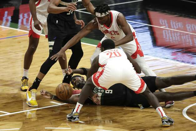 Milwaukee Bucks' Bobby Portis (9) loses control of the ball between Houston Rockets' Khyri Thomas (20) and Danuel House Jr. (4) during the first half of an NBA basketball game Friday, May 7, 2021, in Milwaukee. (AP Photo/Aaron Gash) Photo: Aaron Gash/Associated Press / Copyright 2021 The Associated Press. All rights reserved.