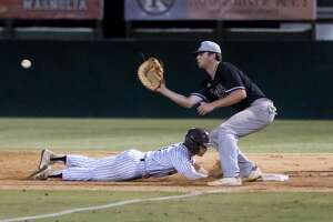 Tyler Middleton #1 of Magnolia dives toward first base before Montgomery first baseman Chase Davis (25) catches a throw during the sixth inning in Game 1 of the Region III-5A bi-district baseball series at Magnolia High School, Thursday, May 6, 2021, in Magnolia.