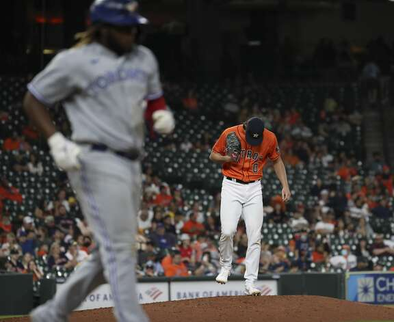 Houston Astros relief pitcher Kent Emanuel (0) waits as Toronto Blue Jays first baseman Vladimir Guerrero Jr. (27) walks to first during the ninth inning of an MLB game Friday, May 7, 2021, at Minute Maid Park in Houston. Photo: Jon Shapley/Staff Photographer / © 2021 Houston Chronicle
