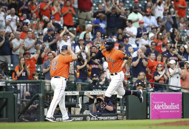 Houston Astros shortstop Carlos Correa (1) celebrates with first base coach Omar Lopez (22) after hitting a home run during the second inning of an MLB game Friday, May 7, 2021, at Minute Maid Park in Houston. Photo: Jon Shapley/Staff Photographer / © 2021 Houston Chronicle
