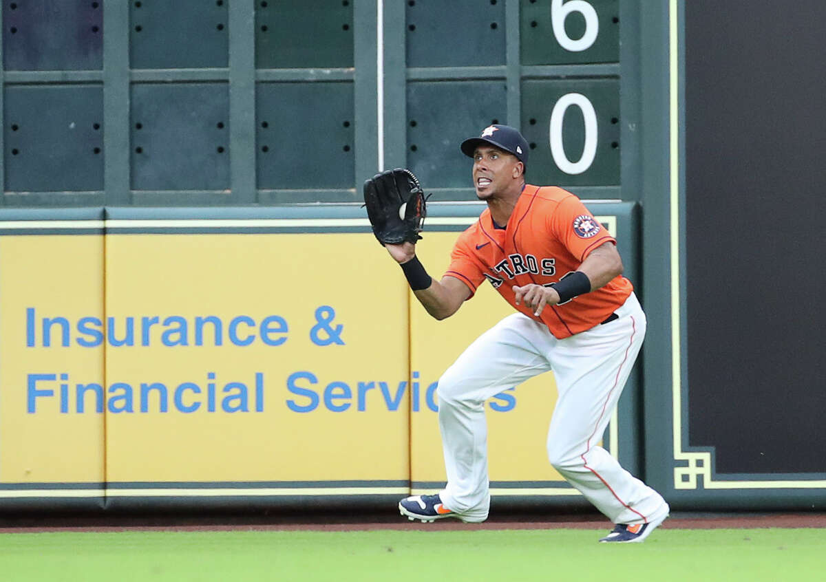 Houston Astros left fielder Michael Brantley (23) catches a flyball from Toronto Blue Jays right fielder Teoscar Hernandez (37) during the first inning of an MLB game on Friday, May 7, 2021, at Minute Maid Park in Houston.