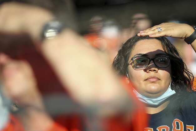 A fan shields her eyes from the setting sun before the start of an MLB game between the Houston Astros and the Toronto Blue Jays on Friday, May 7, 2021, at Minute Maid Park in Houston. The stadium roof was open. Photo: Jon Shapley/Staff Photographer / © 2021 Houston Chronicle