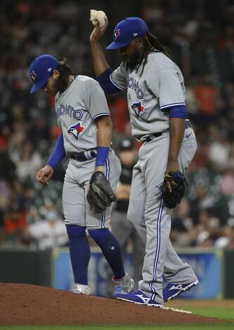 Toronto Blue Jays relief pitcher Rafael Dolis (41) and shortstop Bo Bichette (11) wait for manager Charlie Montoyo to walk to the mound during the eighth inning of an MLB game Friday, May 7, 2021, at Minute Maid Park in Houston. Photo: Jon Shapley/Staff Photographer / © 2021 Houston Chronicle