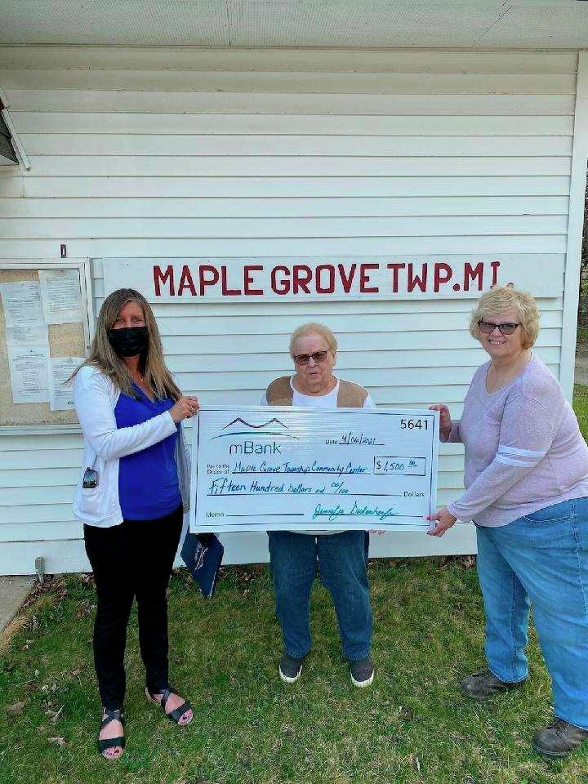 A donation made by mBank for$1,500 is presented by bank manager Lora Tennant to Maple Grove Township clerk Fran Beldo (center) and treasurer Cathy Jeskowski in April to help fund the new Maple Grove Community Center. (Courtesy Photo/Cindy Asiala)