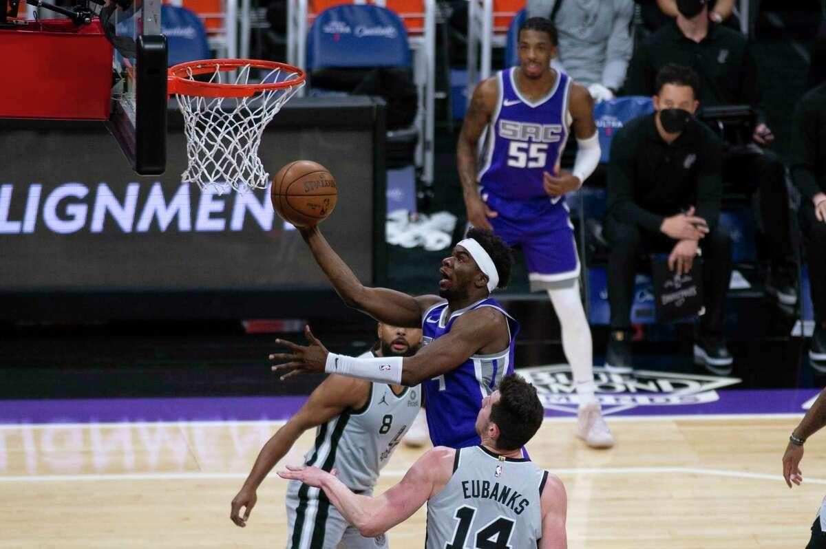 Sacramento Kings guard Terence Davis shoots as San Antonio Spurs guard Patty Mills (8) and forward Drew Eubanks (14) defend during the first quarter of an NBA basketball game in Sacramento, Calif., Friday, May 7, 2021. (AP Photo/Hector Amezcua)