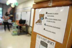 Signs urge students to practice safe hygenic habits to prevent the coronavirus spread at Springdale Elementary School in Stamford, Conn. Tuesday, Sept. 1, 2020. School districts are now deciding whether to offer remote learning in the 2021-22 school year.