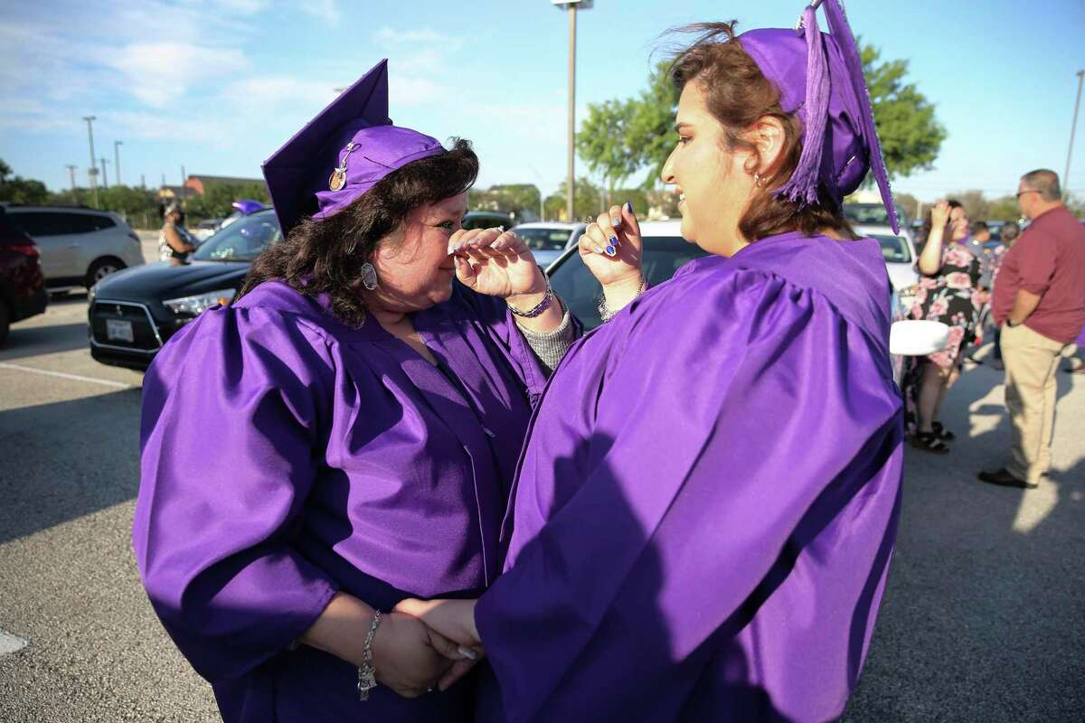 Rebecca Garcia wipes away tears as she and her daughter Monica Garcia wait to participate in Northwest Vista College's a drive-thru graduation ceremony on Friday, May 7, 2021. The two had to take a break from school for different reasons, but they ended up encouraging each other to return in 2018 and after many challenges, they crossed the stage on the same day.