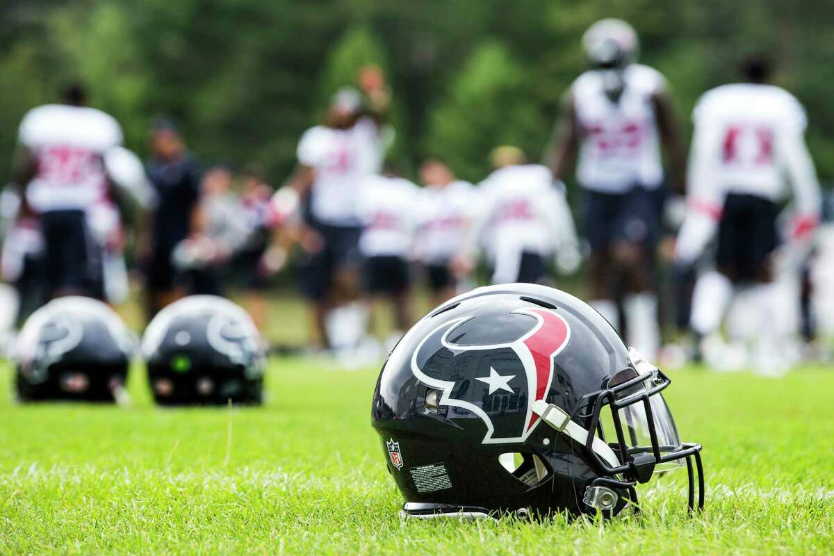 A Houston Texans helmet sits in the grass as the players warm up during training camp at The Greenbrier on Friday, Aug. 11, 2017, in White Sulphur Springs, W.Va.
