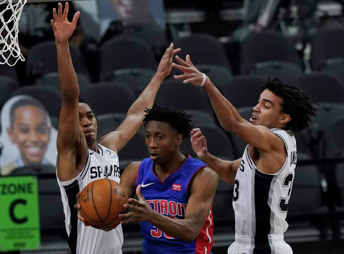 Detroit Pistons guard Saben Lee, center, drives between San Antonio Spurs guard Devin Vassell, left, and San Antonio Spurs guard Tre Jones, right, during the first half of an NBA basketball game in San Antonio, Thursday, April 22, 2021. (AP Photo/Eric Gay)
