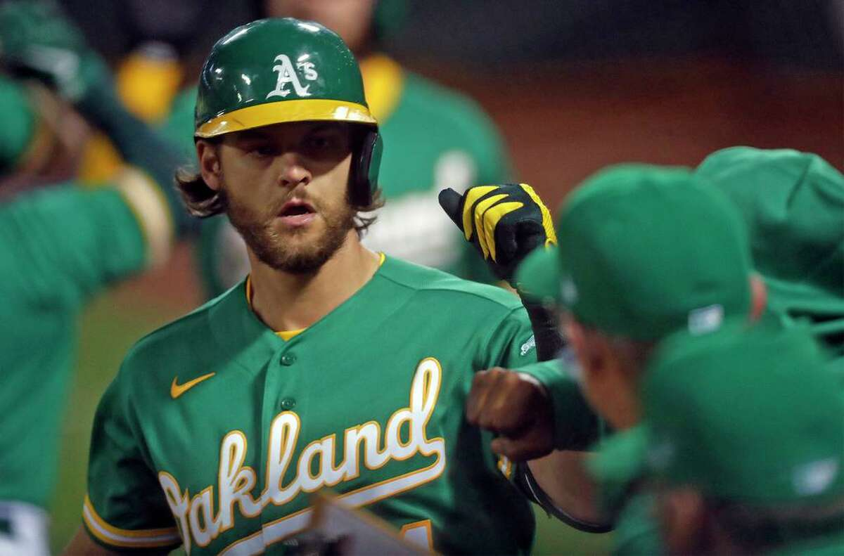 Oakland Athletics' Chad Pinder returns to dugout after his 2-run home run in 7th inning against Houston Astros during MLB game at Oakland Coliseum in Oakland, Calif., on Friday, April 2, 2021.