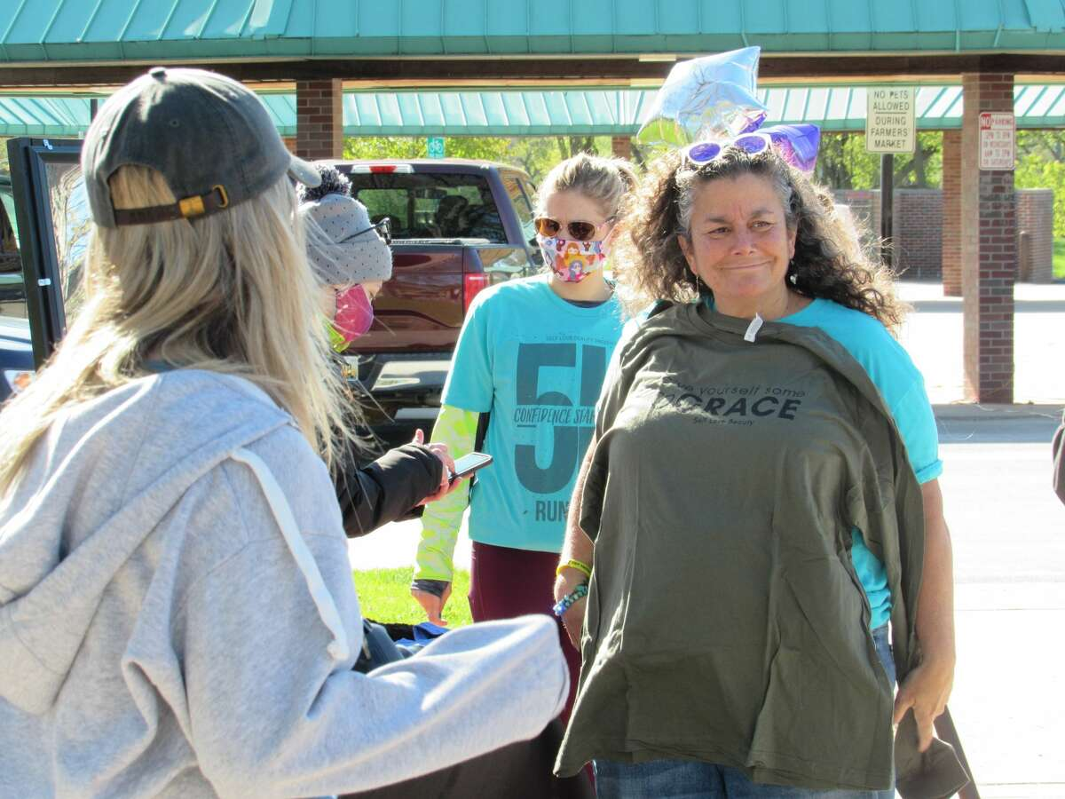 Participants of Self Love Beauty's Confidence Starts Here 5K Run/Walk peruse a selection of t-shirts available for purchase on Saturday, May 8, 2021 in Downtown Midland.