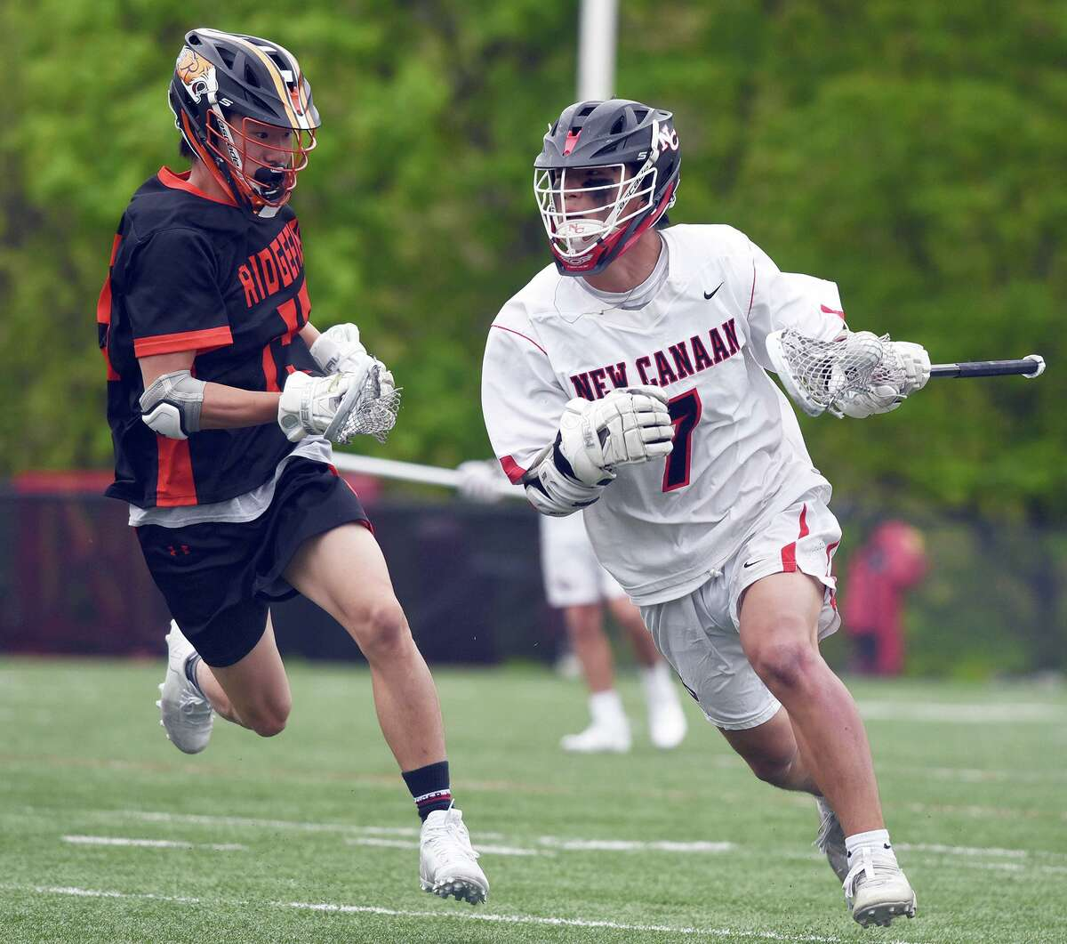 New Canaan's Hayden Shin (7) comes up with the ball during a faceoff, while Ridgefield's Terry Li pursues at Dunning Field in New Canaan on Saturday.