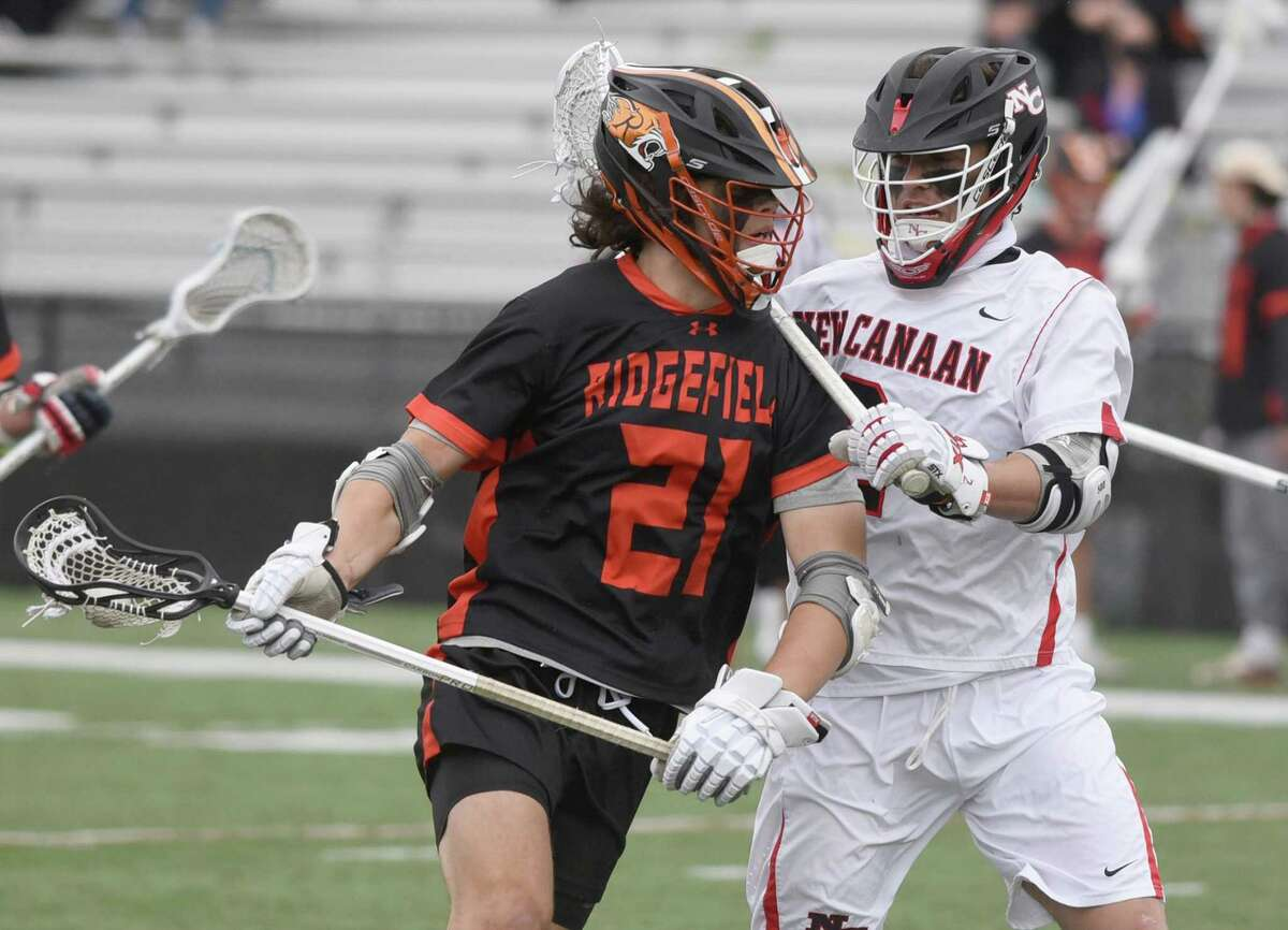 Ridgefield's Joe deGrasse (21) battles New Canaan's Chris Canet (2) at Dunning Field in New Canaan on Saturday.