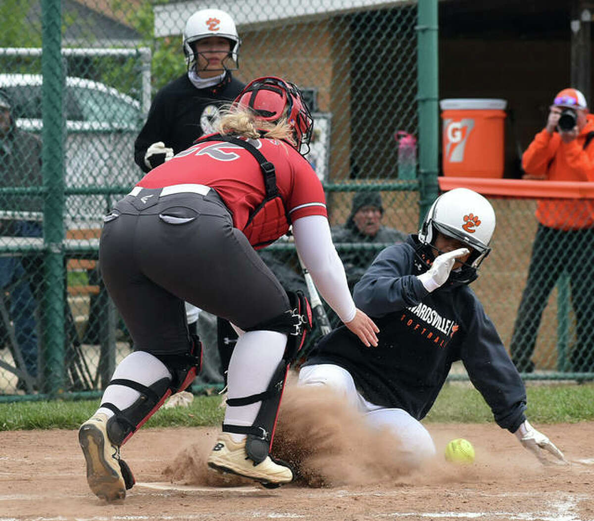 Edwardsville's Zoie Boyd slides safely into home as the throw eludes Alton catcher Lynna Fischer in the second inning of Saturday's game inside the District 7 Sports Complex.