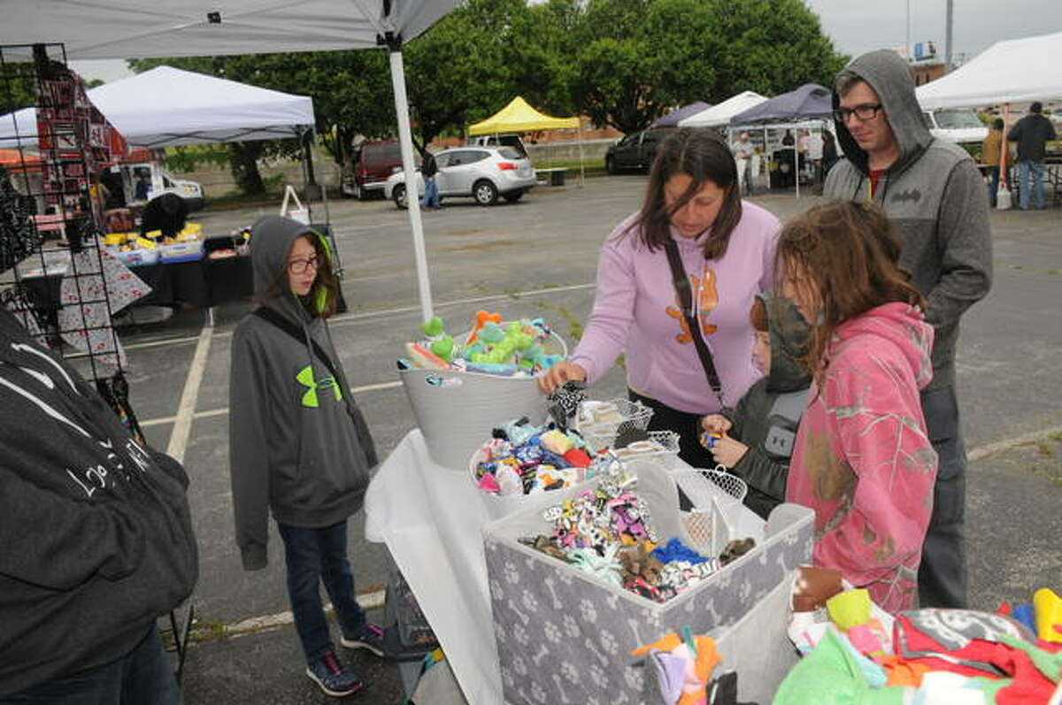 The Brown family from East Alton - first time shoppers at the Alton Farmers' and Artisans' Market - browse the selection of pet toys at a booth on Saturday. The markets are planned every Saturday 8 a.m. to noon through Oct. 16.