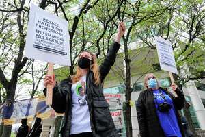 Kate Dempsey, of Darien, left, attends a protest organized by Stamford Mass Defense Coalition in front of the Stamford Government Center in downtown Stamford on Saturday. The rally was held to urge city and state officials to drop all charges against people arrested during march last summer and to protest the death of Stamford resident Steven Barrier.