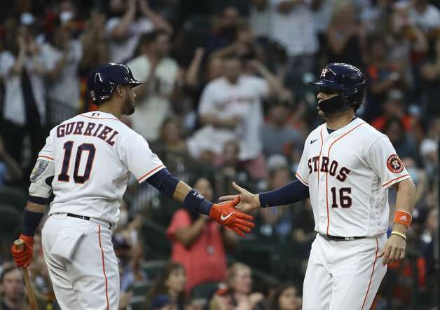 Houston Astros left fielder Aledmys Diaz (16) high-fives first baseman Yuli Gurriel (10) after scoring on a fly-ball by designated hitter Yordan Alvarez (44) during the fifth inning of an MLB game Saturday, May 8, 2021, at Minute Maid Park in Houston. Photo: Jon Shapley/Staff Photographer / © 2021 Houston Chronicle