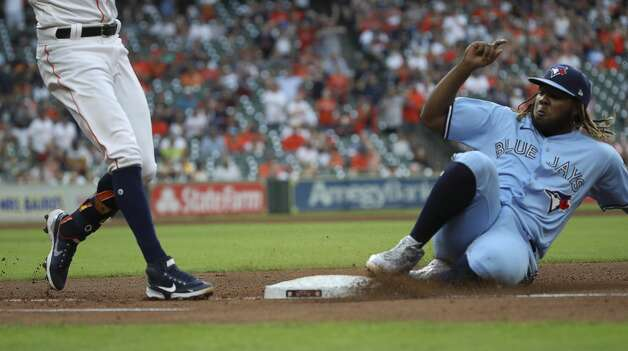 Toronto Blue Jays first baseman Vladimir Guerrero Jr. (27) slides into first base to get out Houston Astros shortstop Carlos Correa (1) during the fourth inning of an MLB game Saturday, May 8, 2021, at Minute Maid Park in Houston. Photo: Jon Shapley/Staff Photographer / © 2021 Houston Chronicle