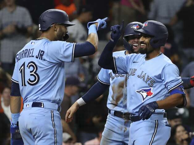 Toronto Blue Jays second baseman Marcus Semien (10), third baseman Cavan Biggio (8) and left fielder Lourdes Gurriel Jr. (13) celebrate after they scored on a home run by Semien during the ninth inning of an MLB game Saturday, May 8, 2021, at Minute Maid Park in Houston. Photo: Jon Shapley/Staff Photographer / © 2021 Houston Chronicle