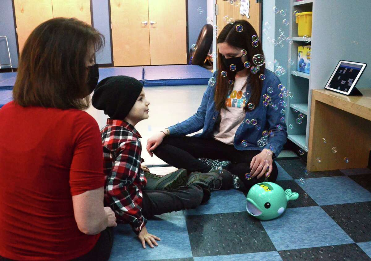 Noah Urbina, 6, catches bubbles with his two therapists at Creative Development, a clinic in Avon, Connecticut. Noah was diagnosed with autism after he turned 3. The two women in the photo said they use bubbles to gain and sustain his attention during speech and occupational therapy sessions.