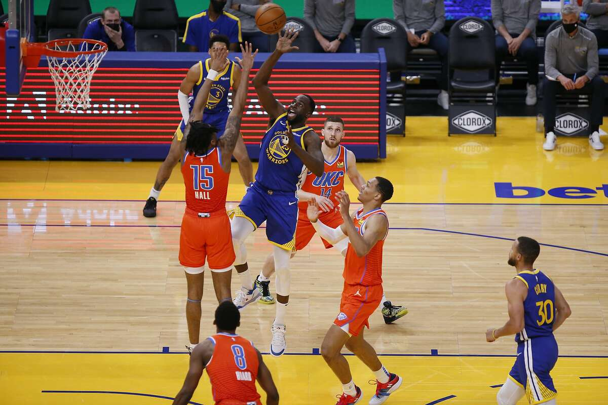 Golden State Warriors forward Draymond Green (23) attempts a two-point shot against Oklahoma City Thunder forward Josh Hall (15) in the first quarter of an NBA game at Chase Center, Saturday, May 8, 2021, in San Francisco, Calif.