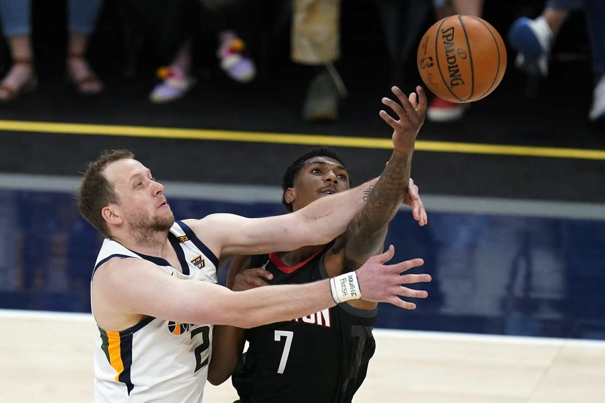Utah Jazz guard Joe Ingles (2) and Houston Rockets guard Armoni Brooks (7) reach for the ball during the first half of an NBA basketball game Saturday, May 8, 2021, in Salt Lake City. (AP Photo/Rick Bowmer)