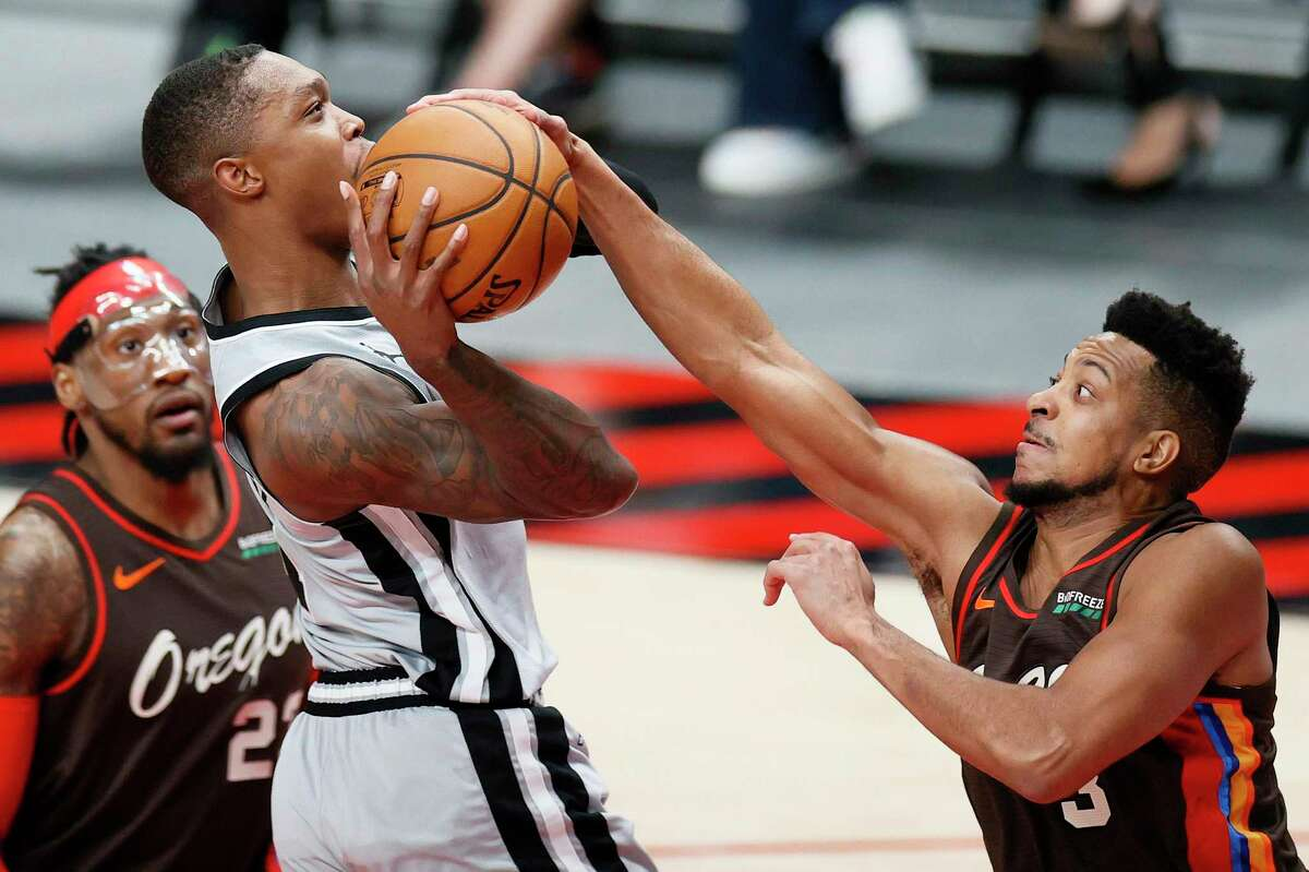 PORTLAND, OREGON - MAY 08: CJ McCollum #3 of the Portland Trail Blazers blocks Lonnie Walker IV #1 of the San Antonio Spurs during the first quarter at Moda Center on May 08, 2021 in Portland, Oregon. NOTE TO USER: User expressly acknowledges and agrees that, by downloading and or using this photograph, User is consenting to the terms and conditions of the Getty Images License Agreement. (Photo by Steph Chambers/Getty Images)