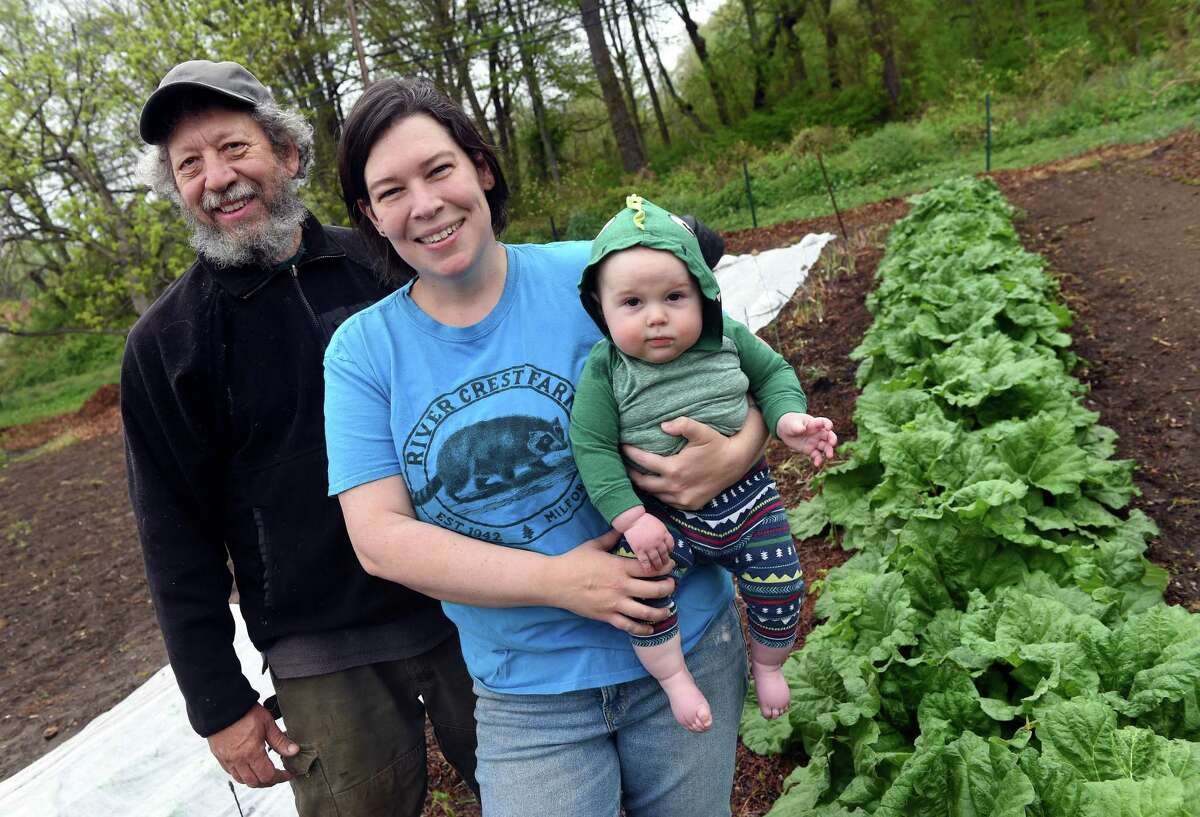 From left, Andy Macri photographed with his daughter, Andromeda Macri, and grandson, Augie Campbell, 8 months, alongside a row of rhubarb at River Crest Farm in Milford on May 5, 2021.