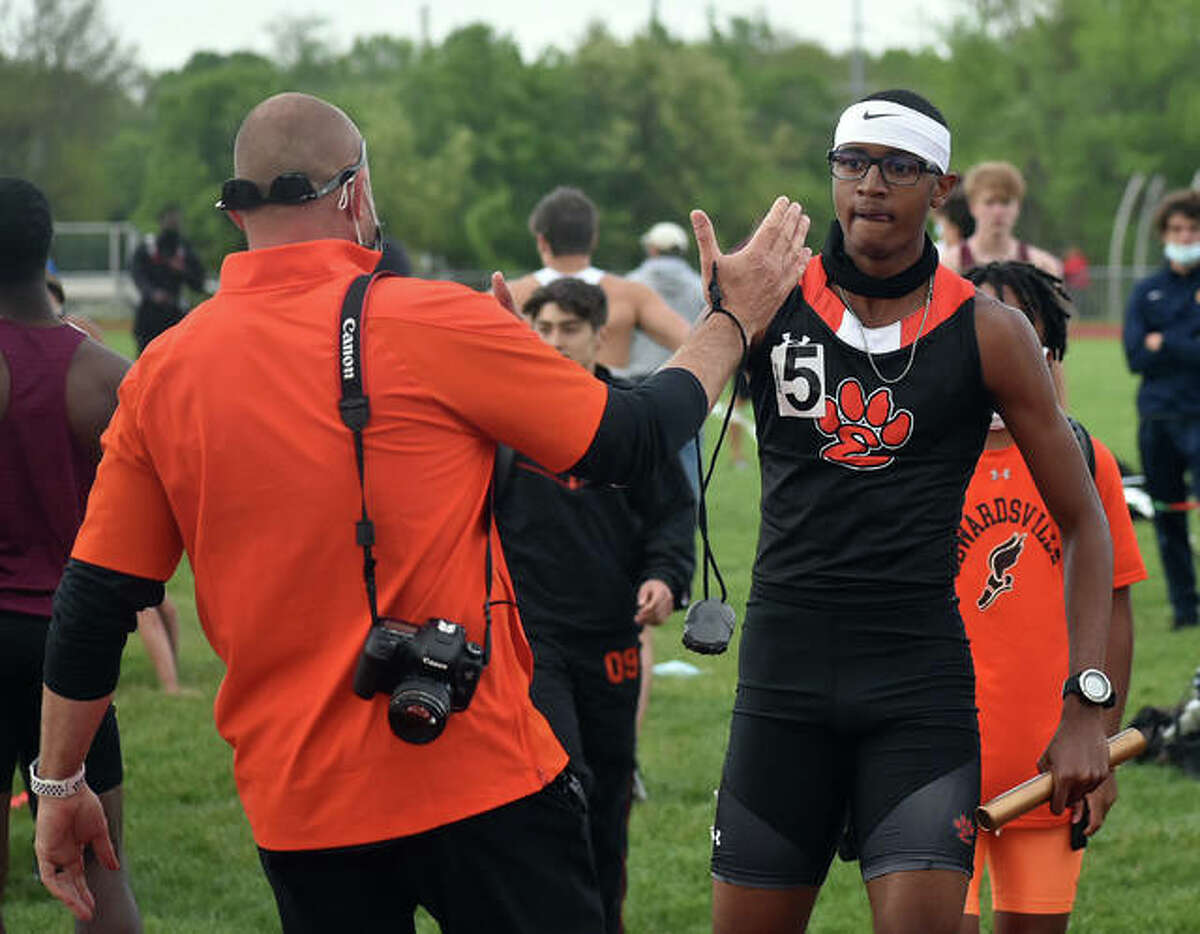 Edwardsville's Brandon Battle (right) is congratulated by Tigers coach Chad Lakatos after Battle ran the anchor leg in a relay victory for the Tigers on Saturday in Edwardsville.