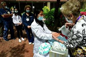 Clinical Coordinator for the Specialty Clinic, Ellen Aversa, receives the blessing of the hands by hospital chaplain Carol Bauer as Norwalk Hosptal staff gather for a dedication ceremony for the newly planted courtyard and the garden Friday, May 7, 2021, in Norwalk, Conn. The courtyard garden was dedicated to the hospital staff who worked during the height of the pandemic. Three new trees, 10 shrubs and 10 perrenial flowers were planted.