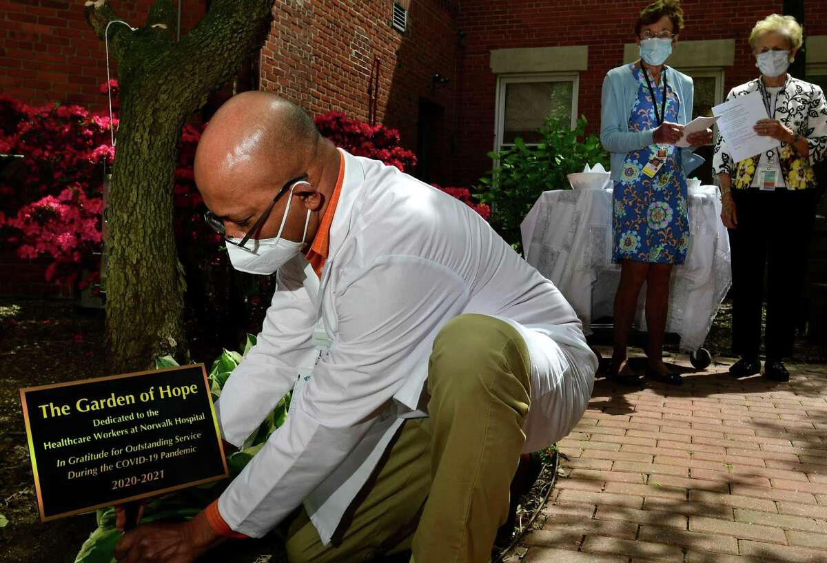 Chaplain Oril Sorvis puts in the sign for the Garden of Hope as Norwalk Hosptal staff gather for a dedication ceremony for the newly planted courtyard and the garden Friday, May 7, 2021, in Norwalk, Conn. The courtyard garden was dedicated to the hospital staff who worked during the height of the pandemic. Three new trees, 10 shrubs and 10 perrenial flowers were planted.