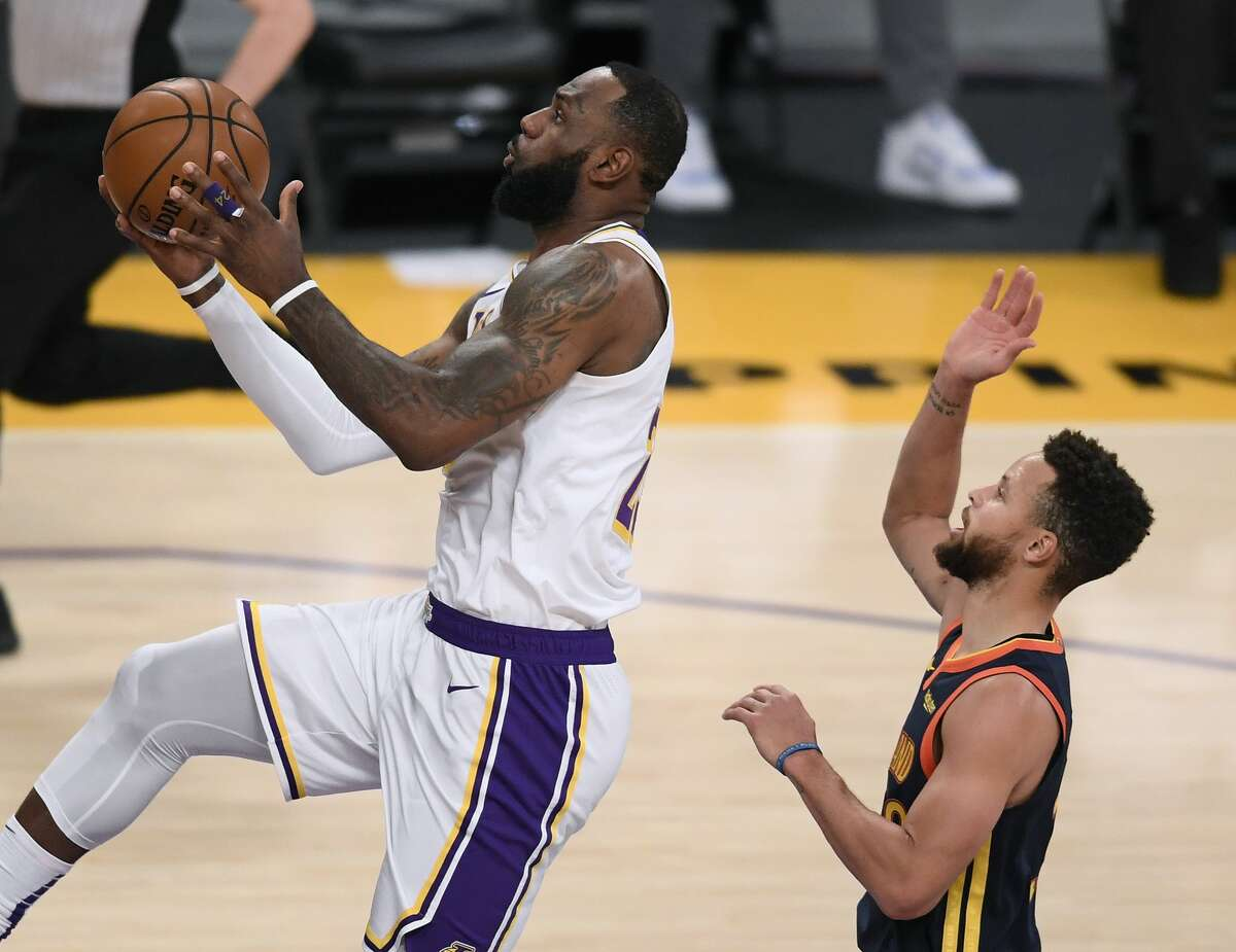 LeBron James of the Los Angeles Lakers scores on a layup past Stephen Curry of the Golden State Warriors on February 28, 2021 in Los Angeles, California.