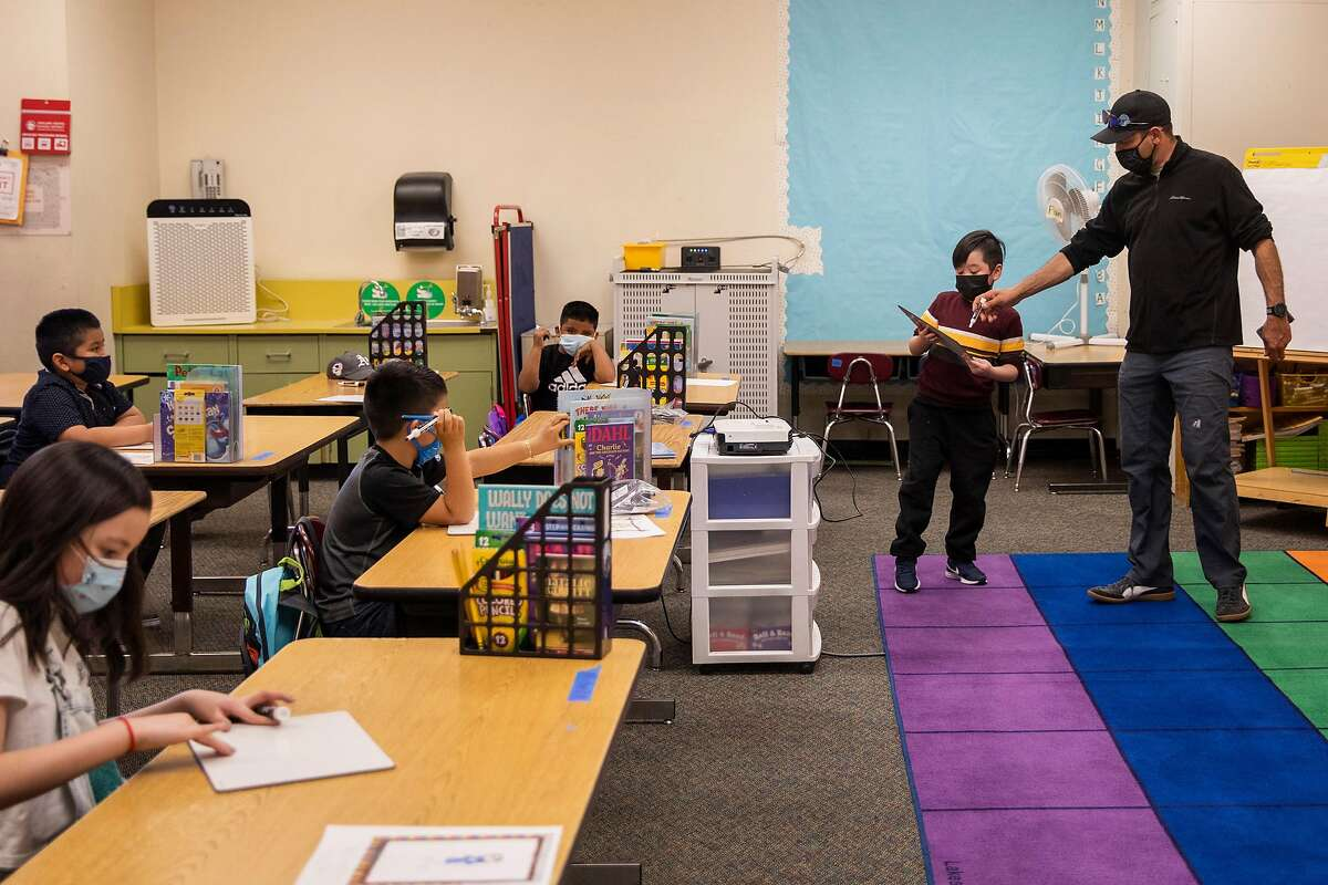 Instructor Chris Eckert helps a student with a math problem at Garfield Elementary School in Oakland in March.