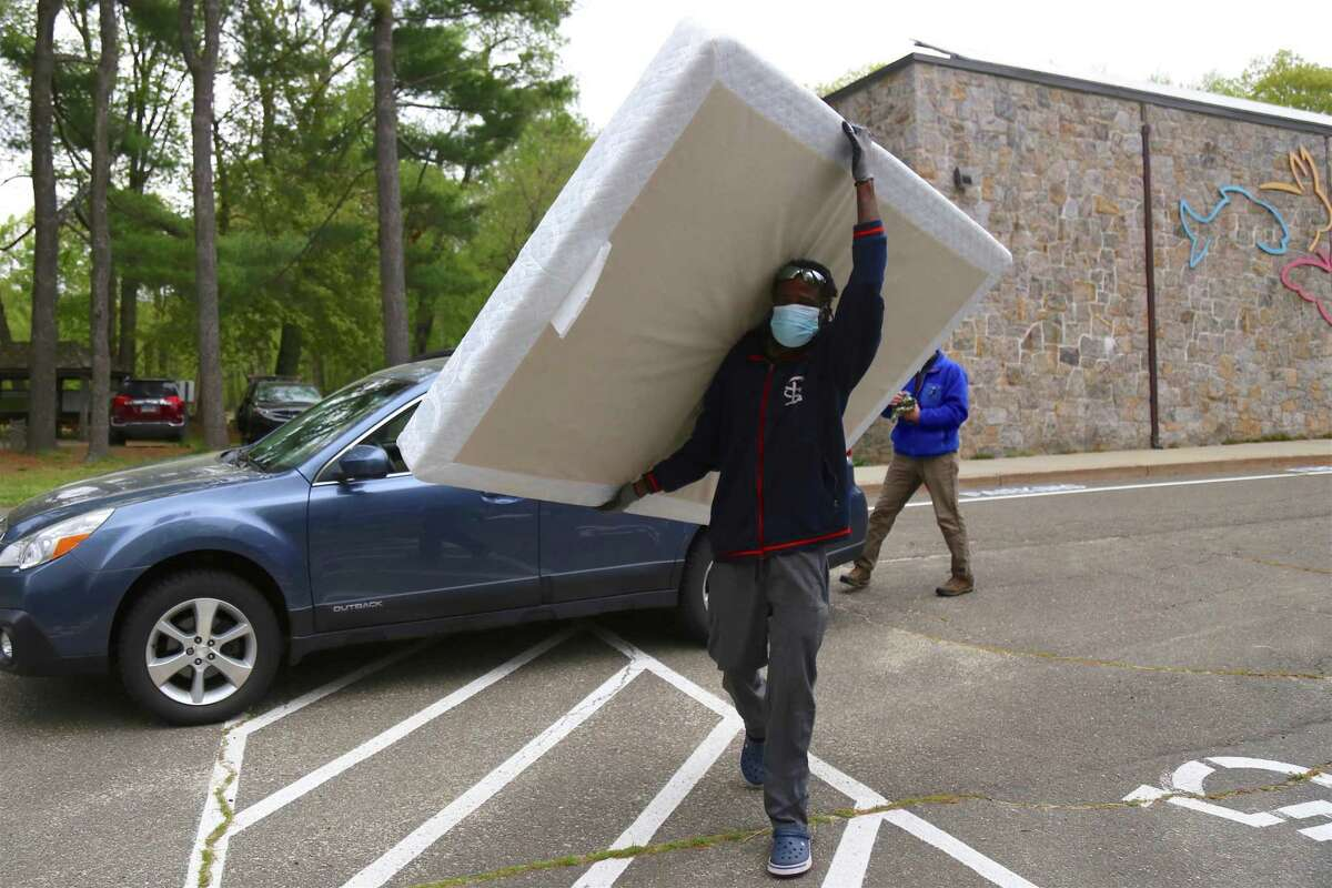 Damon Streater, of Park City Green, totes a mattress for recycling at the recycling event at Earthplace via Sustainable Westport on Saturday, May 8, 2021, in Westport, Conn.