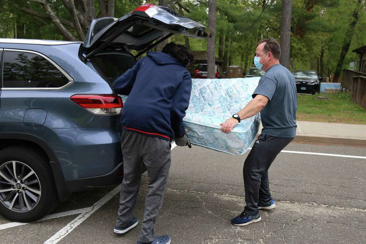 John Caricato, of Westport, hoists a mattress from his car at the recycling event at Earthplace via Sustainable Westport on Saturday, May 8, 2021, in Westport, Conn.