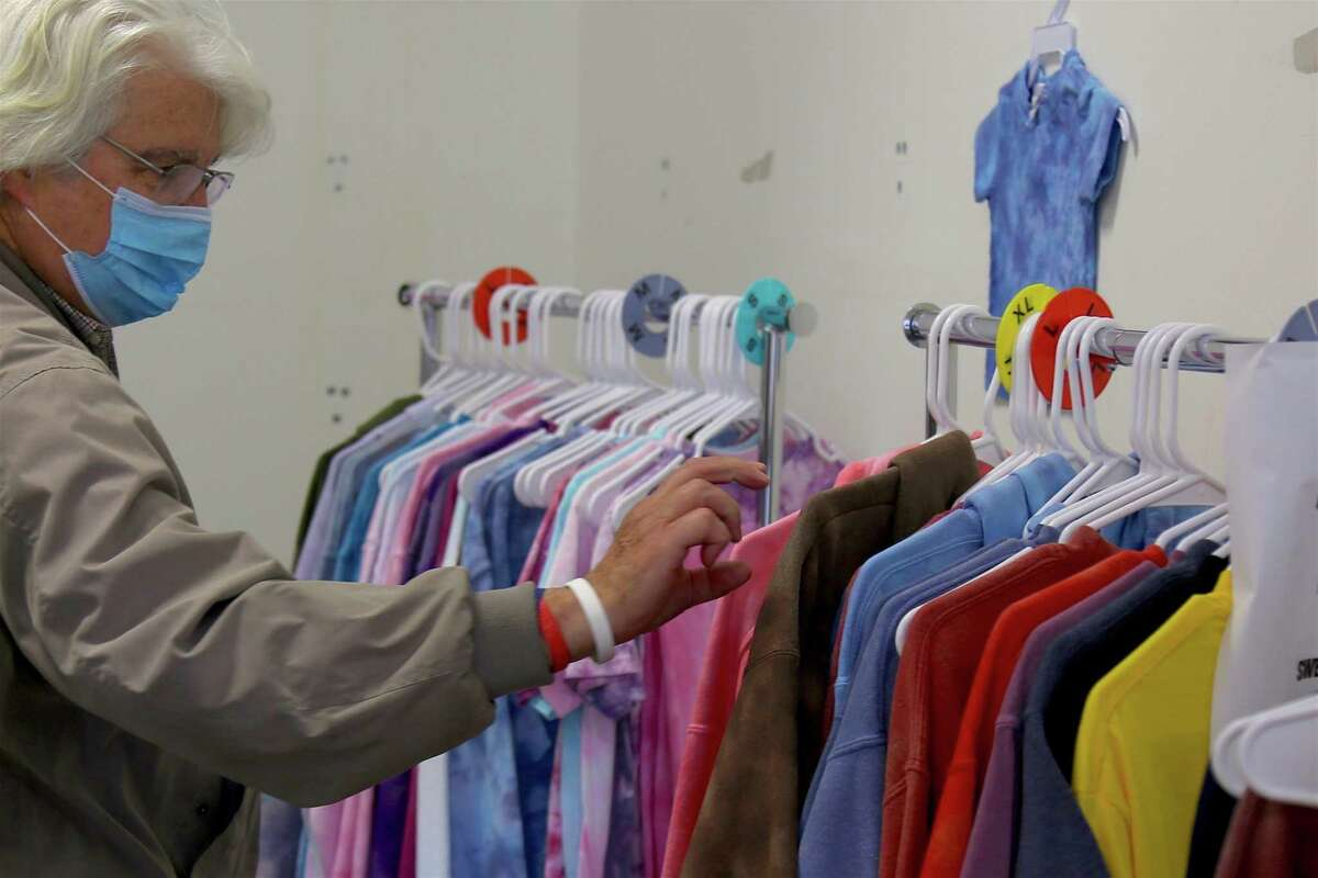 Jay Miggins, of Milford, looks over some merchandise from Fairfield-based Shop Our Dyes at the pop-up market on Henry Carter Drive on Saturday, May 8, 2021, in Fairfield, Conn.
