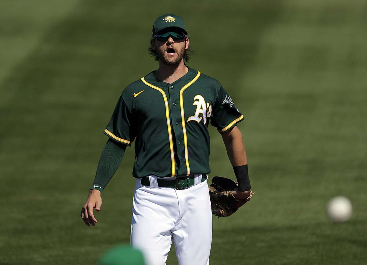 Chad Pinder (4) watches a ball fall foul in the stands after chasing it in right field as the Oakland Athletics played the Los Angeles Angels at Hohokam Stadium in Mesa, Ariz., on Friday, March 5, 2021.