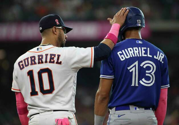 Houston Astros first baseman Yuli Gurriel (10) taps the helmet of his brother Toronto Blue Jays left fielder Lourdes Gurriel Jr. (13) during the sixth inning of an MLB game Sunday, May 9, 2021, at Minute Maid Park in Houston. Photo: Jon Shapley, Staff Photographer / © 2021 Houston Chronicle