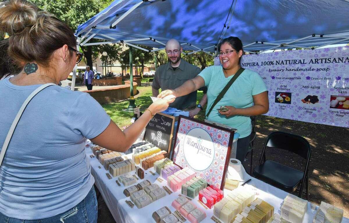 Shoppers visit Conrad Vidrine and Paulina Vidrine's shop, Manipura, on Saturday, Aug. 3, 2019, at Jarvis Plaza during the Farmers Market.