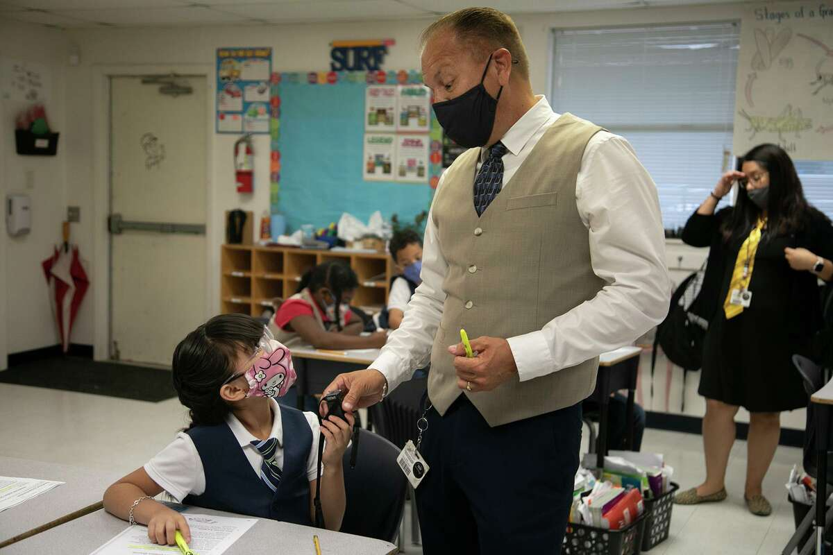 """Teacher Hugo Ibarra talks with student Maliyah on a recent Tie Tuesday at Larkspur Elementary School. The weekly event """"gives them a sense of pride,"""" Ibarra said of his second-grade students."""