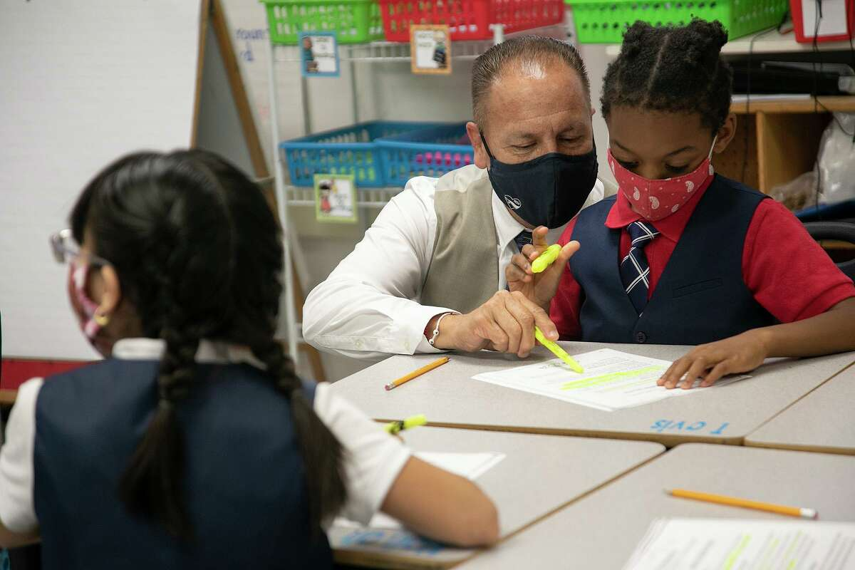 A masked teacher works with a student at Larkspur Elementary School in May. Young kids can't get vaccinated for COVID - and yet masking is optional.