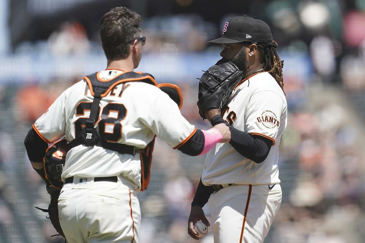 San Francisco Giants pitcher Johnny Cueto, right, stands on the mound as catcher Buster Posey (28) approaches during the third inning of a baseball game against the San Diego Padres in San Francisco, Sunday, May 9, 2021. (AP Photo/Jeff Chiu)